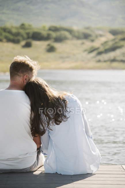 Женщина, сидя рядом на причал, опираясь на мужское плечо. — стоковое фото