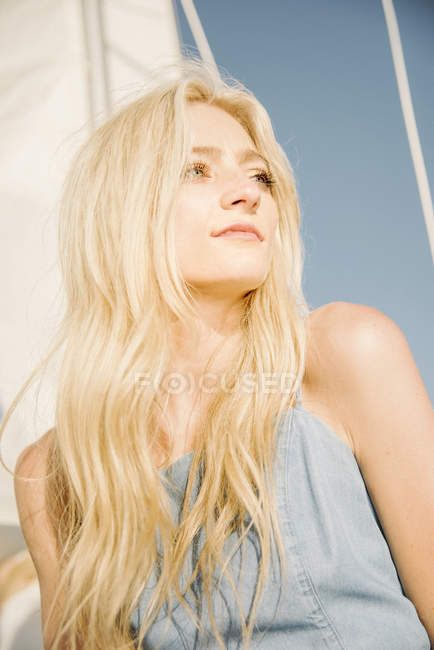 Young blonde woman under sail on boat against blue sky, portrait. — Stock Photo