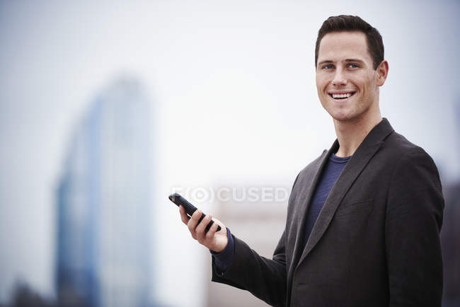 Young businessman standing on rooftop, holding smartphone and looking in camera. — Stock Photo