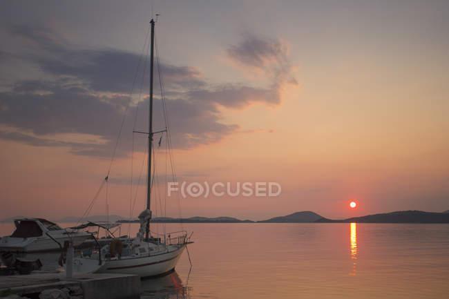 Pôr do sol sobre o Mar Mediterrâneo com iate ancorado na costa . — Fotografia de Stock