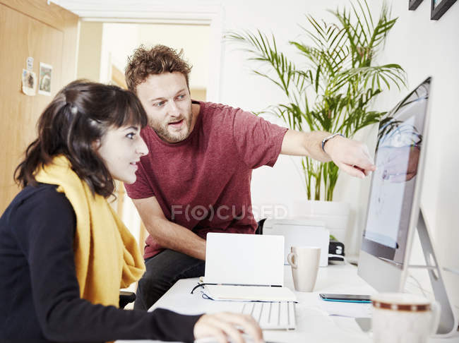 Two coworkers working together in office and looking at computer screen. — Stock Photo
