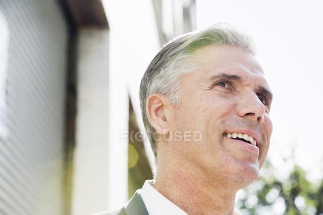 Людина з сивим волоссям, стоячи на вулиці, дивлячись і посміхається — стокове фото
