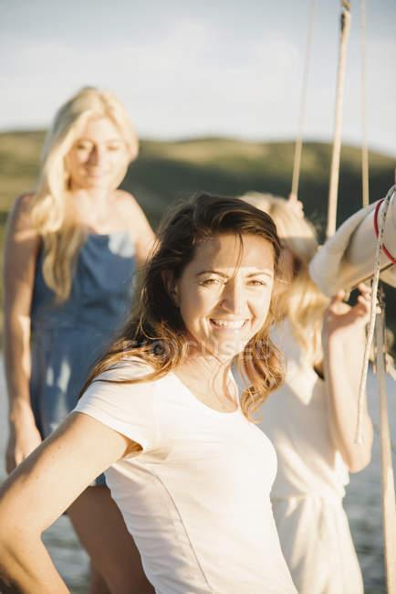 Reife Frau mit blonden Töchtern auf Segelboot im Sonnenlicht. — Stockfoto