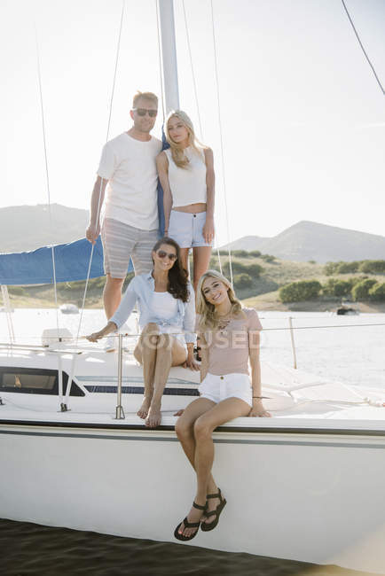 Mature parents with teenage daughters relaxing on sailboat. — Stock Photo
