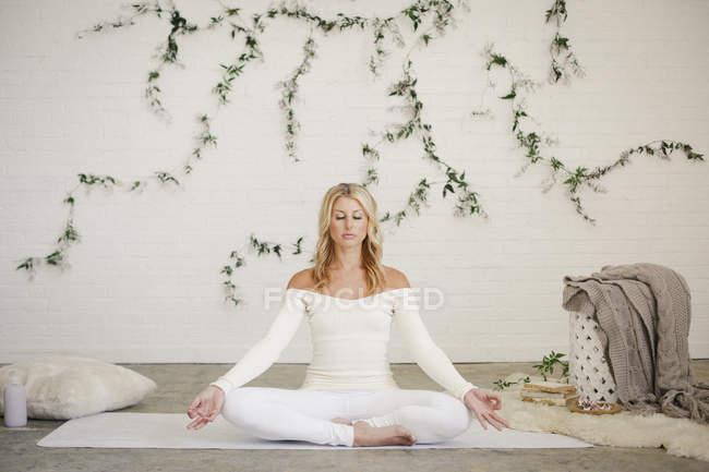 Блондинка сидит на белом коврике для йоги и медитирует. . — стоковое фото