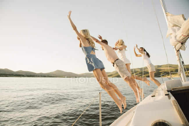 Parents with teenage daughters jumping off sailboat into lake water. — Stock Photo