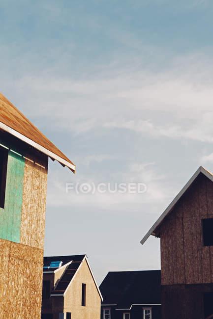 Обрізаний вид на дахи будинків проти синього неба в приміському районі. — стокове фото