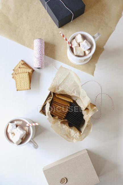 Tasses de cacao chaud avec guimauves maison et biscuits sucrés en papier . — Photo de stock