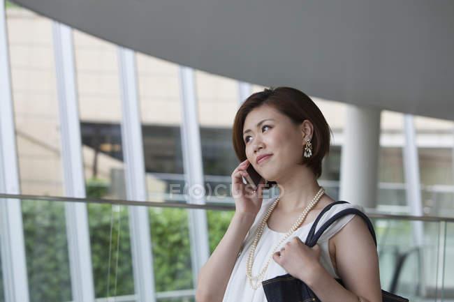 Frau telefoniert auf Gehweg in Bürogebäude. — Stockfoto
