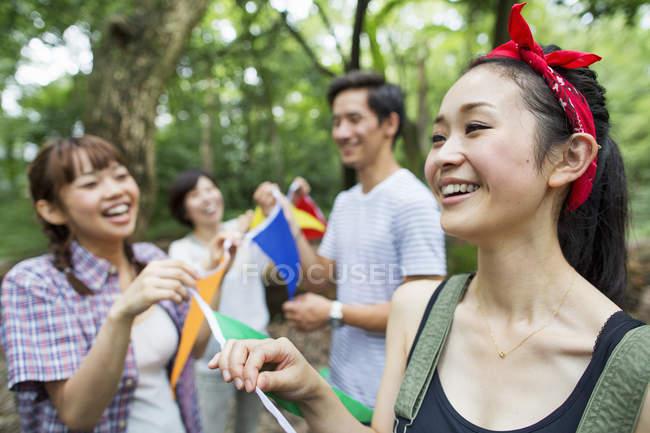 Groupe d'amis, tenant des drapeaux lors d'une fête en plein air en forêt — Photo de stock