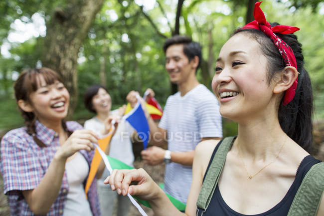 Group of friends holding flags at outdoor party in forest. — Stock Photo