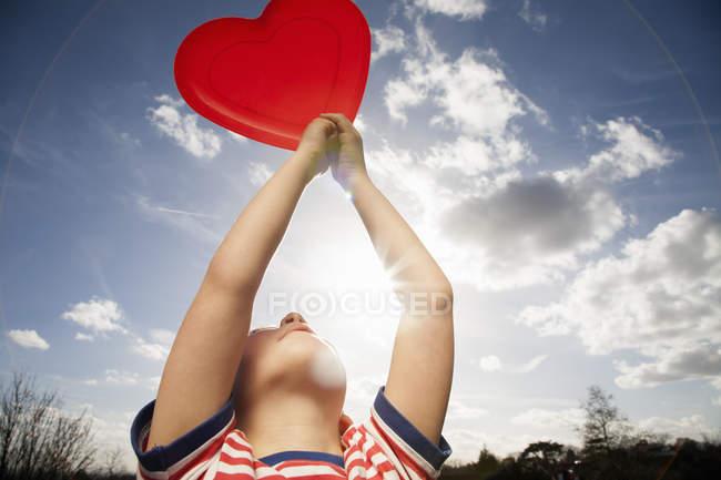 Vista de ângulo baixo da criança mantendo a forma de coração vermelho ao ar livre. — Fotografia de Stock