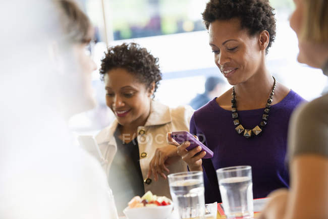 Women checking mobile phones at meeting with friends in restaurant. — Stock Photo