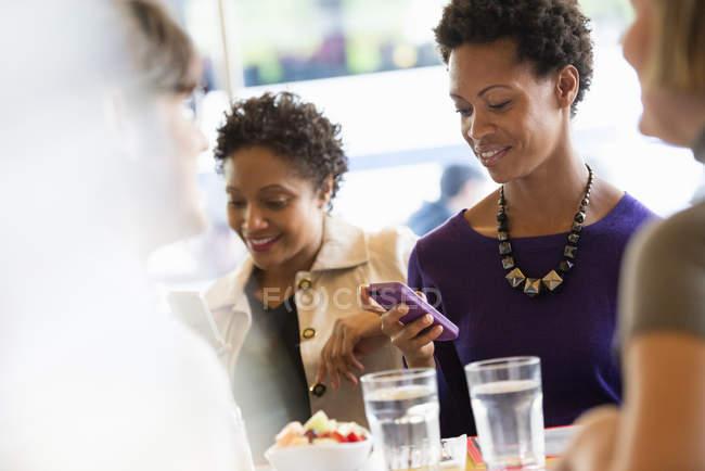 Mulheres, verificação de telemóveis na reunião com amigos em restaurante — Fotografia de Stock