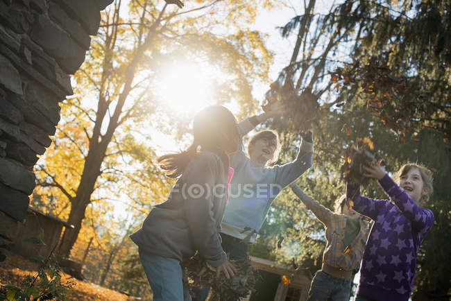 Children playing outdoors and throwing fallen leaves in autumn sunshine. — Stock Photo