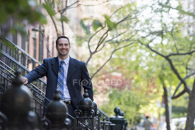 Man in business suit standing on steps of residential building on street. — Stock Photo