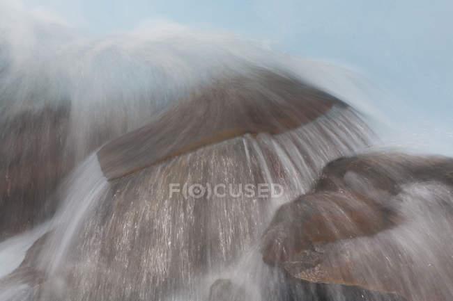 Размытые вид потока воды, протекающей по камням — стоковое фото