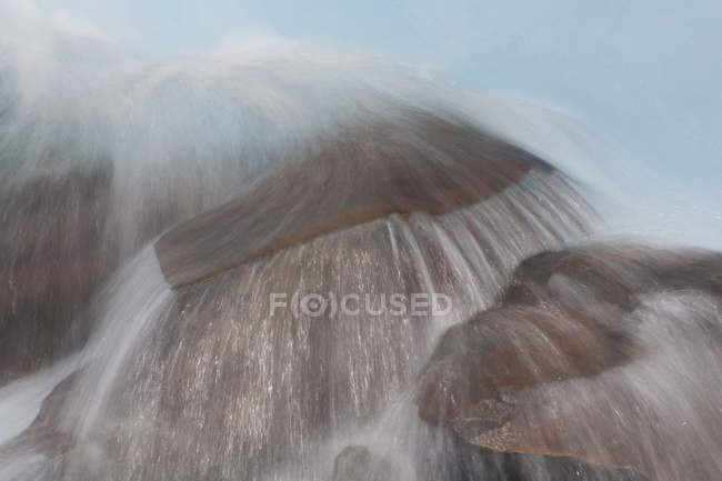 Blurred view of water stream flowing over rocks. — Stock Photo