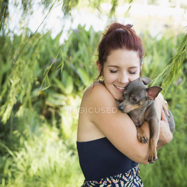 Середині дорослу жінку притискаючи чихуахуа собака. — стокове фото
