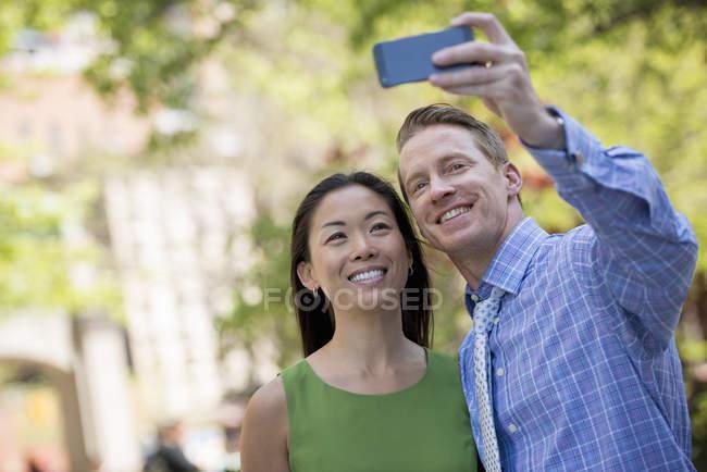 Homme et femme tenant selfie smartphone sur rue — Photo de stock