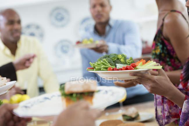 Обрізаний зору людей вручення пластинами продовольства через фуршету. — Stock Photo