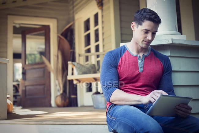Homem usando tablet digital no alpendre na casa do campo . — Fotografia de Stock