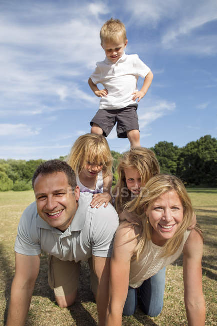 Boy climbing on parents and sisters while playing in park. — Stock Photo