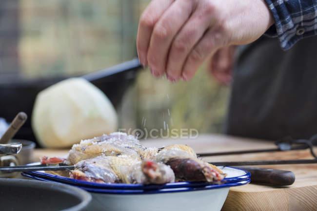 Sale di spruzzatura di mano maschile su pelle di uccello spatchcocked su tavolo . — Foto stock