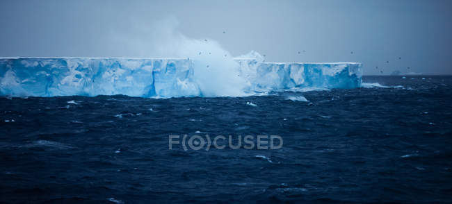 Large steep iceberg floating on spraying water with waves. — Stock Photo