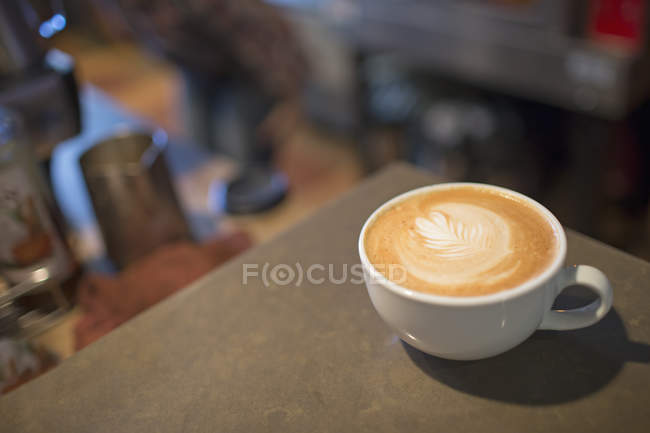 Full white cup of fresh coffee with frothed milk top. — Stock Photo