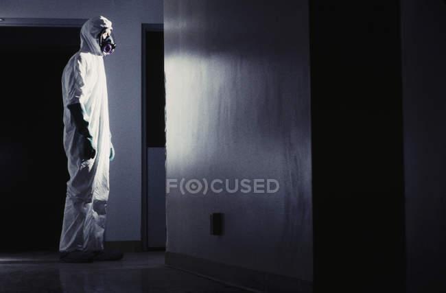 Traje de hombre en materiales peligrosos protección frente a luz en el pasillo. - foto de stock