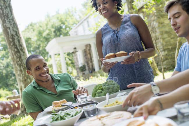 Amigos y familiares se reúnen alrededor de la mesa en el jardín rural . - foto de stock