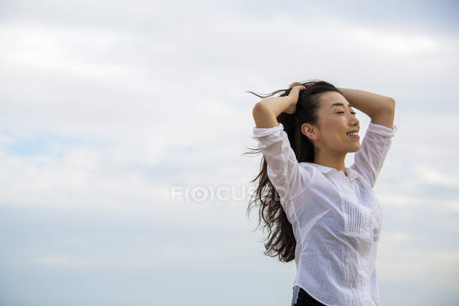 Long-haired woman enjoying breeze outdoors against cloudy sky. — Stock Photo