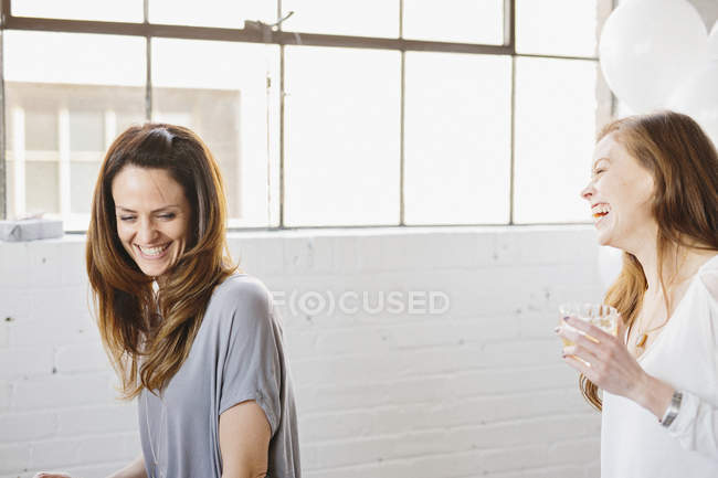 Two women laughing together in room decorated with balloons. — Stock Photo