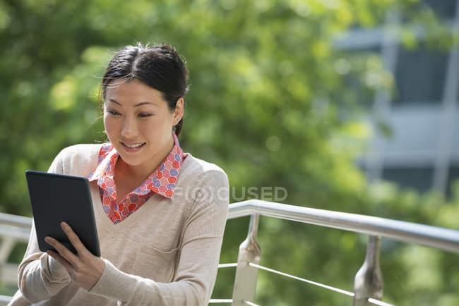 Metà donna adulta utilizzando tablet digitale nel parco cittadino . — Foto stock