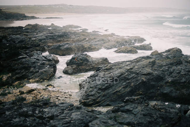 Rocks on beach by sea with waves breaking and mist rising. - foto de stock