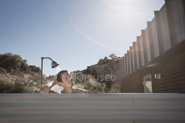 Man taking shower outdoors on terrace of house under sunlight. — Stock Photo