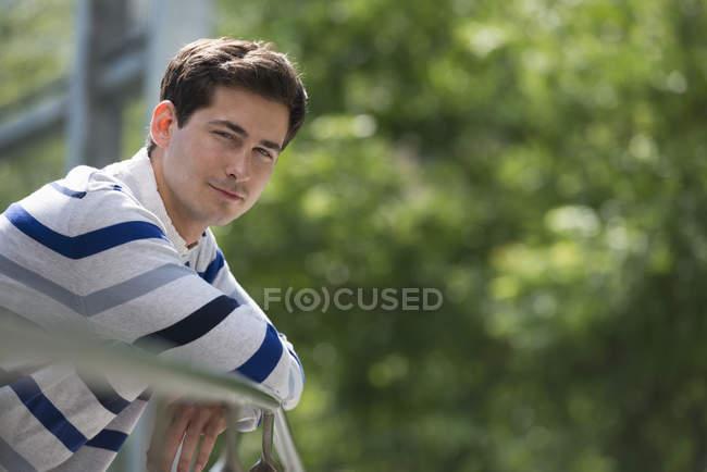 Jeune homme appuyé sur la rampe et regardant à la caméra dans le parc . — Photo de stock