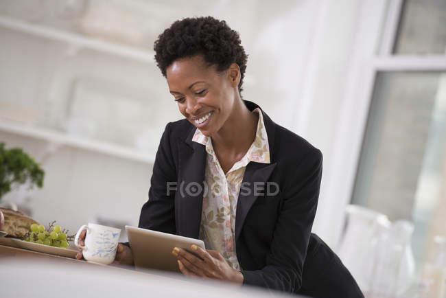 Mulher de casaco preto usando tablet digital e segurando copo no escritório . — Fotografia de Stock