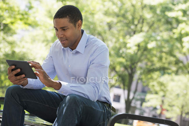 African american man using digital tablet while sitting on park bench. — Stock Photo
