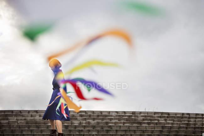 Artista donna in movimento linea di bandiere durante la performance alle scale di strada . — Foto stock