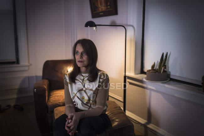 Женщина средних лет сидит с грустным выражением лица на диване в темной комнате . — стоковое фото