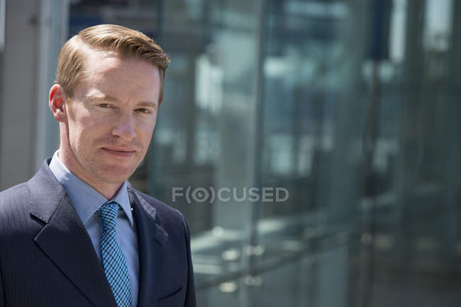 Man in business suit outside building with glass exterior. — Stock Photo