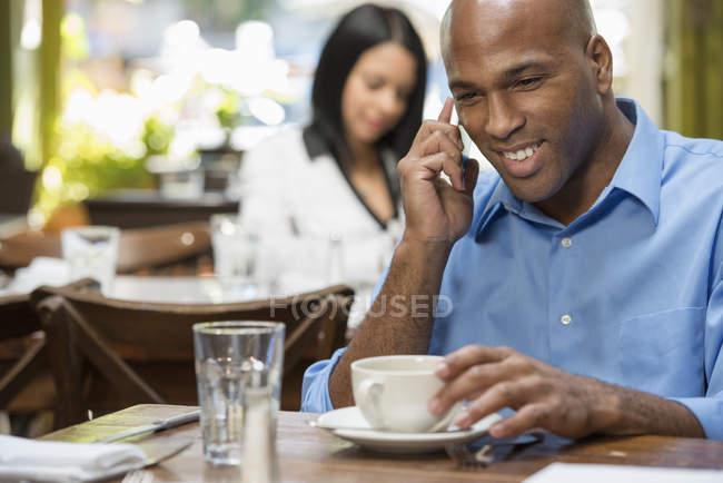 Homme adulte moyen parlant au téléphone dans un café avec une femme en arrière-plan . — Photo de stock