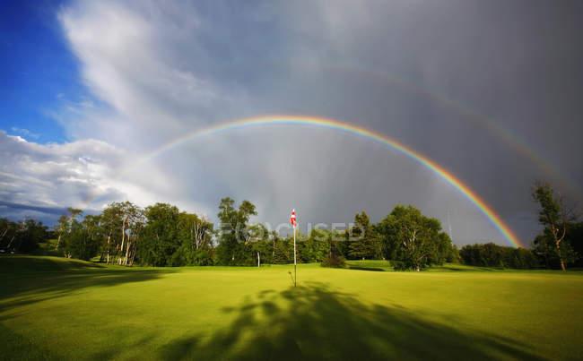 Double arc-en-ciel dans le ciel au-dessus du golf vert . — Photo de stock