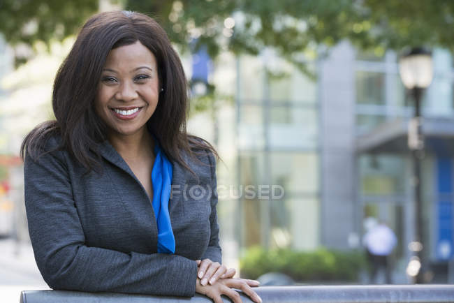 Mujer de negocios en traje gris apoyada en barandilla y sonriendo en el centro de la ciudad . - foto de stock