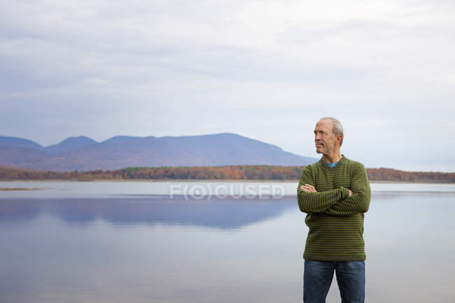 Mature man with arms folded by water of lake in mountains. — Stock Photo
