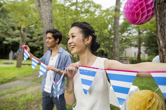Young couple hanging lanterns and flags on trees in woods. — Stock Photo