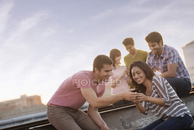Paar mit Telefon mit Freunden auf Dachterrasse mit party. — Stockfoto