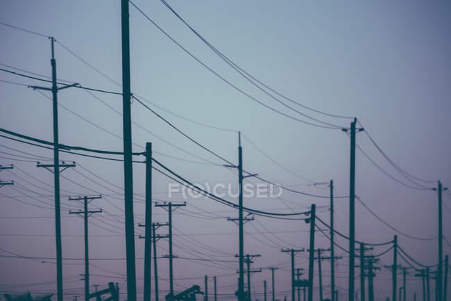 Strommasten auf einem Ölfeld bei Sonnenuntergang in Kalifornien, USA — Stockfoto
